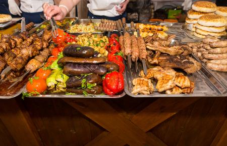carnes y verduras: Cierre de vista de la generosidad de carnes y verduras cocidas bien ordenados en bandejas metálicas con Clientes Selección de elementos con unas pinzas en el restaurante bufé o Food Festival Foto de archivo