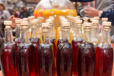 corked: Close Up Still Life of Corked Bottles Containing Homemade Gourmet Red Soda Arranged Neatly in Rows on Table at Outdoor Food Festival