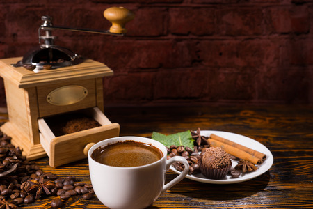 Open grinder with powder against dark background besides white mug of hot coffee and a tasty chocolate dessert