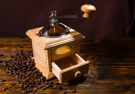 olden day: Square wooden coffee grinder with little open drawer and metal crank over table with dark background and scattered dark beans