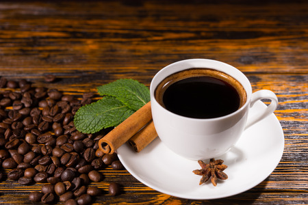 White mug of fresh black coffee by star anise and cinnamon sticks and pile of beans on wooden table