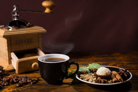 Still Life of Cup of Brewed Coffee Next to Truffle on Plate of Cinnamon Sticks, Star Anise and Other Spice Garnishes on Wood Table Scattered with Roasted Coffee Beans