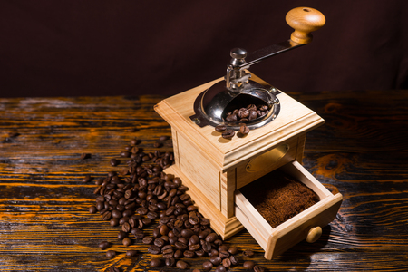 olden day: High Angle Still Life View of Traditional Wooden Hand Grinder with Fresh Ground Coffee on Rustic Wooden Table with Roasted Coffee Beans and Copy Space