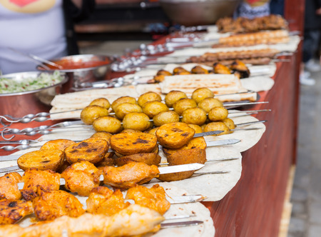 carnes y verduras: larga mesa con la fila de pinchos kebob llenos de varias carnes y verduras en la cafetería con los servidores no identificables