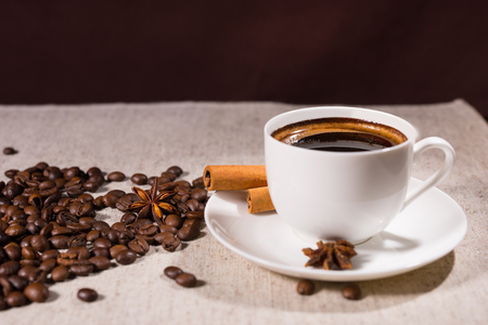 Loose coffee beans beside mug and star anise on table covered by light colored canvas