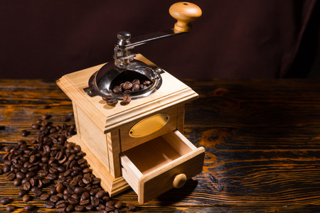 olden day: Single hand crank square shaped wooden coffee grinder with blank label and open drawer over table with dark background and scattered dark beans