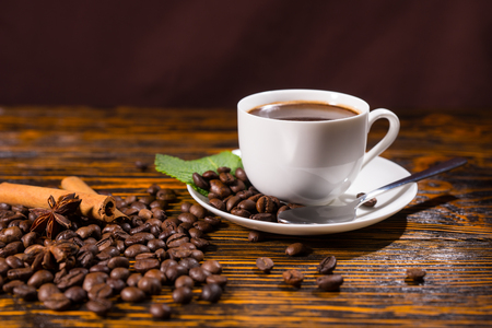 addictive drinking: Close Up Still Life of White Cup and Saucer Containing Fresh Brewed Coffee Resting on Rustic Wooden Table Top Scattered with Roasted Coffee Beans, Cinnamon Sticks and Star Anise