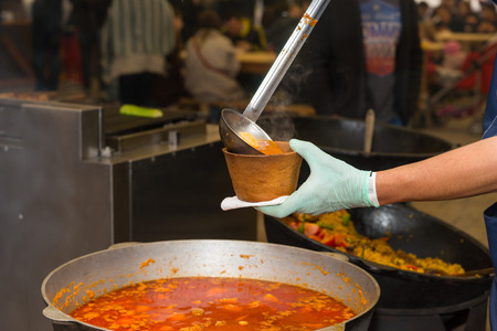 gloved: Close Up of Unrecognizable Person with Gloved Hand Serving Bowl of Spicy Soup from Large Cauldron into Small Take Out Bowl in Restaurant or Outdoor Food Festival