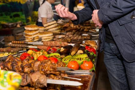 carnes y verduras: Cierre de vista de irreconocible Hombre que mira la abundancia de carnes y verduras cocinadas dispuestas en bandejas metálicas en abundante buffet o restaurante Food Festival Foto de archivo