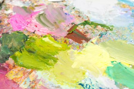 painter's palette: Bright blended oil paint on a palette  on a milticolored professional painters palette