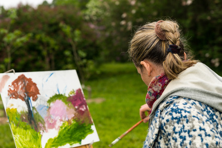 finishing touches: Female undistracted artist painting with oils and acrylics finishing touches working  on a trestle and easel  during an art class in a park Stock Photo