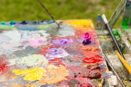 pallette: Différents frais peinture à l'huile mélangée sur la palette d'un artiste brillant milticolored avec pinceaux professionnels