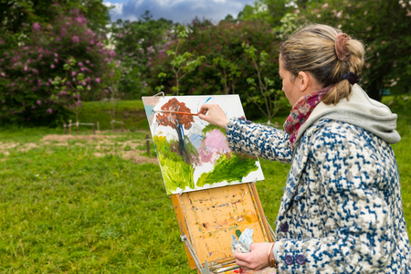 finishing touches: Female contemplative painter painting with oils and acrylics finishing touches working  on a trestle and easel  during an art class outdoors Stock Photo