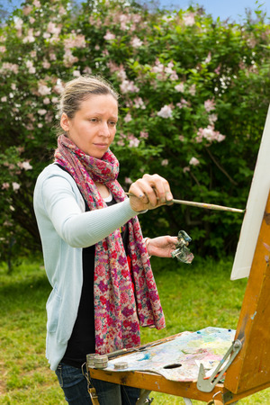 in the open air: Pensive female painter panting her masterpiece holding paintbrush in the open air with background of beautiful trees