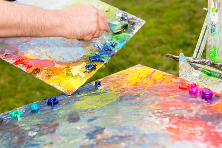 pallette: Artist Mixing Paint By Palette Knife And Getting Ready To Work In The Open Air