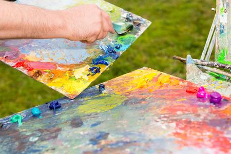 Artista miscelazione vernice da Spatola e si prepara a lavorare in Open Air