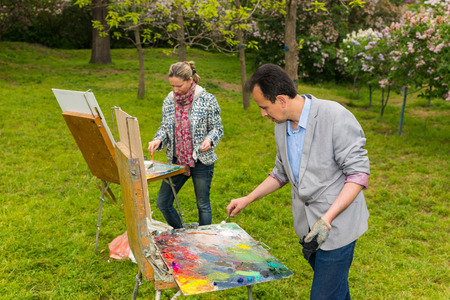 trestle: Fashionable male and female painter working outdoors in the park or garden on a trestle and easel mixing paint with a paletteknife during an art class Stock Photo