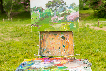 pallette: Close up painters sketchbook with picture and colorful palette of blended oil paints outdoors Stock Photo