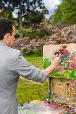 finishing touches: Male artist painting with oils and acrylics finishing touches working  on a trestle and easel  during an art class in a park
