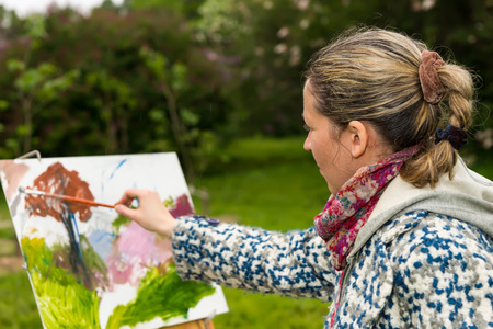 finishing touches: Female contemplative artist painting with oils and acrylics finishing touches working  on a trestle and easel  during an art class in a park