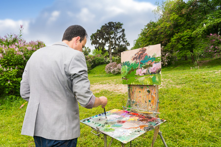 brush painting: Middle-aged fashionable male painter mixing colors of oils and acrylics paint with a paintbrush on a palette in a park  during an art class Stock Photo