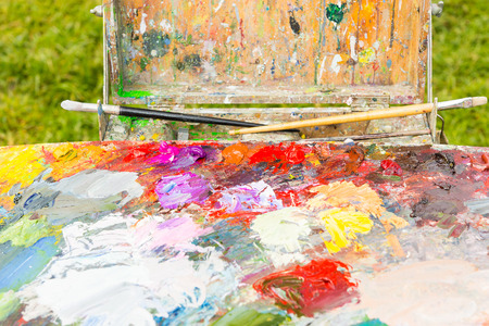 pallette: Professional painters sketchbook  with multicolored palette of blended oil paints with paintbrushes outdoors