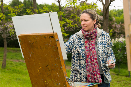 finishing touches: Young female undistracted artist painting with oils and acrylics finishing touches working  on a trestle and easel  during an art class in a park