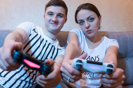 mesmerized: Cheerful and attractive young couple of boy and girl so passionated about the process of a game that even simulating the game steering movements holding  consoles in front of them in a close up frontal view sitting on the sofa at home