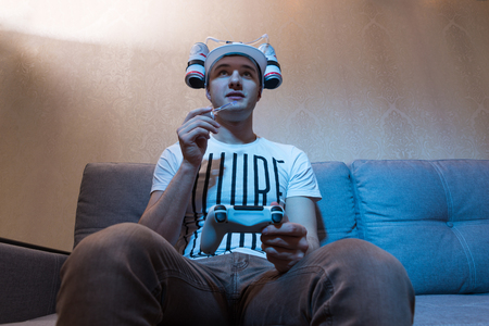 avid: Bottom view of young male football supporter in a goofy hat shaped like a football with flasks of liquid on either side and a tube to his mouth holding a console and playing video game Stock Photo