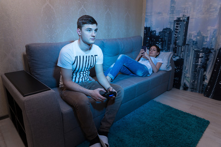 mesmerized: Young man  playing a video game holding a console while his young wife lying on the sofa and surf the Internet by her mobile phone at home