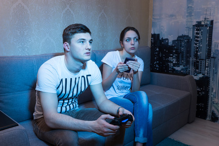 mesmerized: Fascinated young man playing a video game with his girlfriend sitting near him on the sofa and monitor the process of his game at home in a relaxed atmosphere Stock Photo