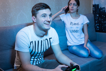 mesmerized: Happy man  playing a video game with a beaming smile of pleasure sitting on the sofa at home while his girlfriend talking on the phone disappointed by his behavior