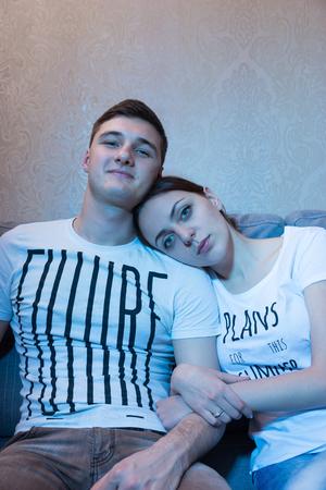 amigos abrazandose: Pareja rom�ntica, sentado en embrance en un sof� juntos delante de un televisor en casa en un ambiente relajado y ver la televisi�n