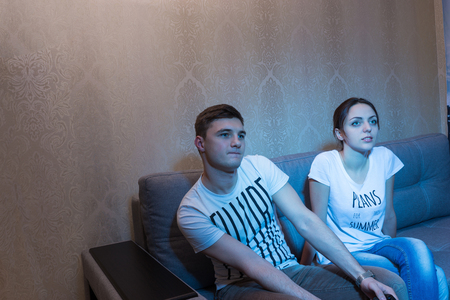 mesmerized: Young couple passionate about the process of a game while sitting on the sofa in front of a TV at home in a relaxed atmosphere