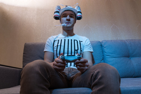 avid: Bottom view of attractive male football supporter in a goofy hat shaped like a football with flasks of liquid on either side and a tube to his mouth holding a console and playing video game