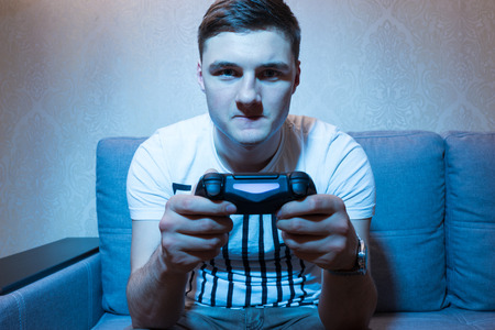 mesmerized: Young man playing a video game with a very serious and concentrated face as he holds his console in front of him in a close up frontal view sitting on the sofa at home Stock Photo