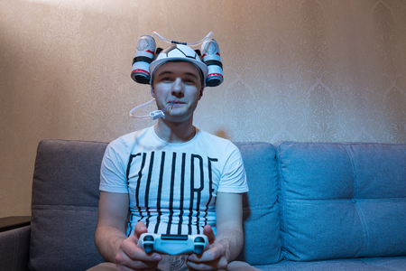 avid: Young male football supporter in a goofy hat shaped like a football with flasks of liquid on either side and a tube to his mouth holding a console and playing video game Stock Photo