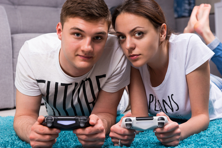 looking towards camera: Young attractive pair lying on a rug in their living room playing video games looking towards the camera