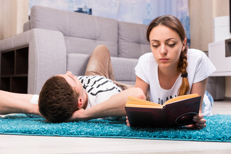 camaraderie: Attractive girl reading book near her boyfriend lying on a rug in their living room  in a relaxed atmosphere