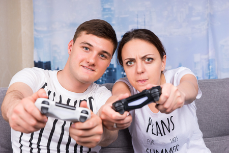 mesmerized: Cheerful and attractive young pair so passionated about the process of a game that even simulating the game steering movements holding  consoles in front of them in a close up frontal view sitting on the sofa at home Stock Photo