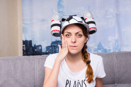 Female football supporter worried about the team in a goofy hat shaped like a football with flasks of liquid on either side sitting on a sofa at home