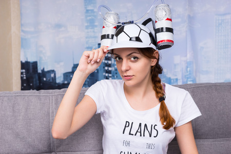 avid: Female football supporter in a goofy hat shaped like a football with flasks of liquid on either side sitting on a sofa at home