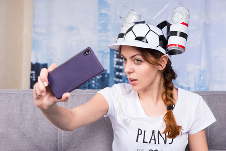 avid: Female football supporter taking selfie by her cell phone in a goofy hat shaped like a football with flasks of liquid on either side sitting on a sofa at home