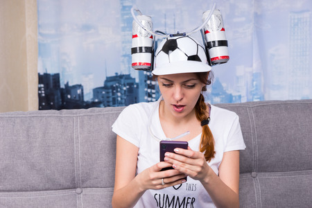 avid: Woman with braid drinks beer from device on cap surf the Internet by her cell phone sitting on a sofa at home Stock Photo