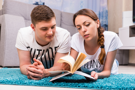 camaraderie: Young couple lying on a rug in their living room and reading a book in a relaxed atmosphere