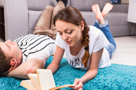 shrewd: Cheerful girl reading book near her boyfriend lying on a rug in their living room  in a relaxed atmosphere