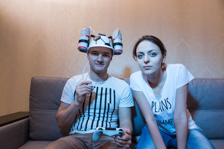 Young male supporter in a goofy hat shaped like a football with flasks of liquid on either side and a tube to his mouth holding a console an sitting on the sofa with his girlfriend