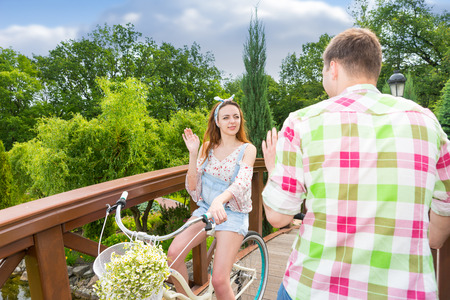 tryst: Young girl meet a boy in green and red plaid shirt while riding on a bike with flowers in a basket on footbridge in a beautiful park Stock Photo