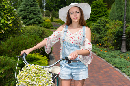 tryst: Female wearing a white hat standing on footpath near her bicycle with a bouquet of little white flowers in a basket in a park