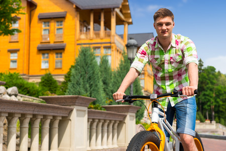 Male riding a colorful yellow bicycle past a matching yellow painted house on a brick paved road, low angle view